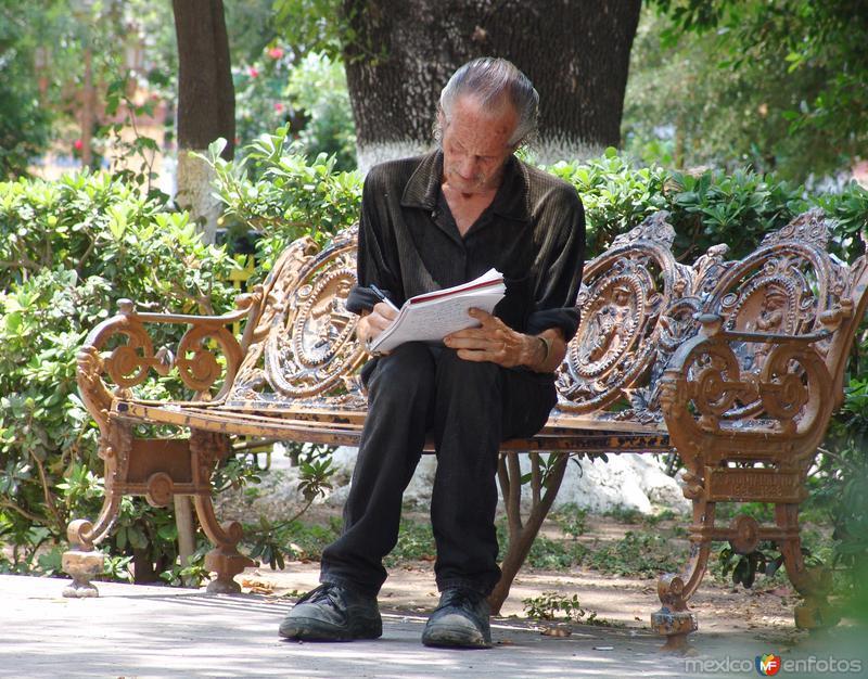 Señor escribiendo en la plaza principal
