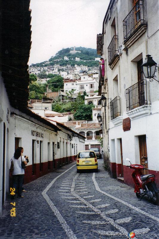 Calle empedrada con figuras en el centro de Taxco, Guerrero