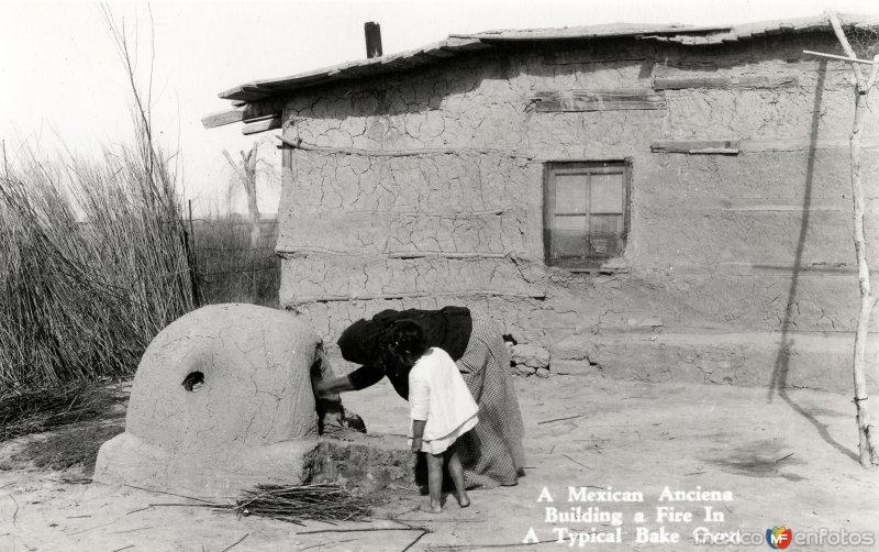 Una anciana encenciendo fuego en un horno tradicional