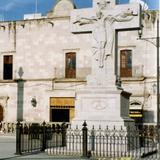 Cruz de cantera en el atrio de la Basílica y al fondo el Palacio Municipal. 2005